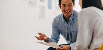 Korean graphic designer sharing ideas during meeting in modern office studio